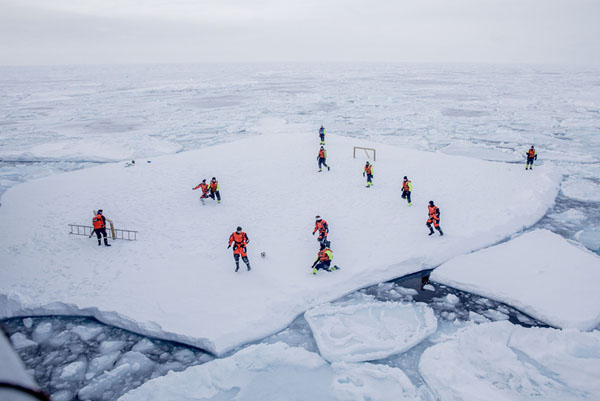KV Svalbard's crew play soccer as they are protected from polar bears by armed guards in the arctic environment in the sea around Greenland